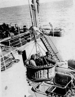 Whalers moving between whaling ships at sea in a similar basket.