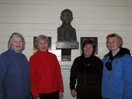 C.A Larsen's granddaughters and a cousin (second right) pose with the bust of Larsen in the church.