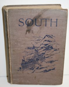 Photo of brown book with blue illustration of the small life boat in the ocean near rugged land and the title SOUTH
